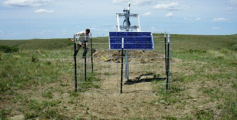 An EarthScope field engineer piles dirt on the sealed vault for Transportable Array station I28A near Midland, S.D. The station is powered by solar energy and continuously transmits its data via cellphone.