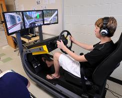 Teenager Travis Keeler uses a simulator during driver education class at West Forsyth High School in Cumming, Ga., last fall.