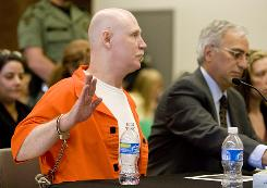 In this June 10 picture, Ronnie Lee Gardner raises his restrained hand as he is sworn in before speaking at his commutation hearing at the Utah State Prison in Draper, Utah. Next to him is his attorney Andrew Parnes.