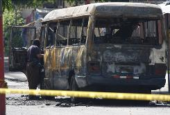 A police officer inspects a burnt bus in San Salvador Monday.