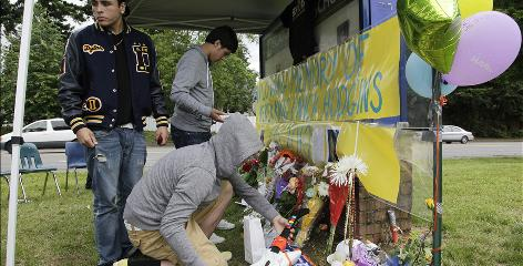 In Federal Way, Wash., Michael Bowles kneels to add a memento to a memorial for Decatur High School seniors Derek King and Nicholas Hodgins, who died in a crash June 9, just days before graduation.