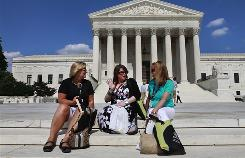 Teachers, from left, Adele Dalesandro of St. Charles, Ill., Julie Hershenberg of Carrolton, Texas, and Jilly Harry, of Knoxville, Tenn., sit on the steps of the U.S. Supreme Court after attending a program there with the Supreme Court Summer Institute for Teachers, in Washington.