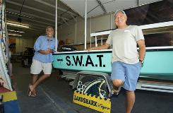 Jimmy Buffett, right, and Mark Castlow lean against the S.W.A.T. boat that Buffett is sending to the Gulf to help with oil spill cleanup.