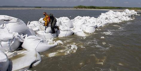 A Guardsman negotiates a barrier created by the National Guard using 2,000-pound bags of sand to protect Louisiana's Scofield Bay from encroaching oil.