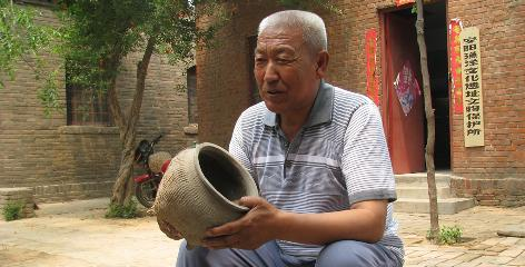Long Zhenshan, 64, a farmer and antiques collector, shows off an ancient cooking pot, one of more than 3,000 pieces he has found.