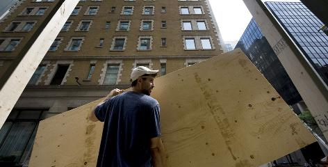 Workers install plywood on street-level condos in Toronto in preparation for protests expected during the G-20 summit.