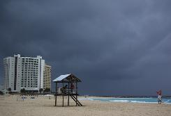 Overcast skies hang over a deserted beach in Cancun, Mexico, on Saturday, as tropical storm Alex nears the region.