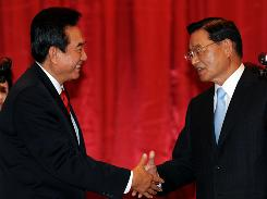 Chen Yunlin, left, the head of a semiofficial Chinese agency negotiating with Taiwan, shakes hands with Taiwan's envoy Chiang Ping-kun, chairman of the Straits Exchange Foundation, in Chongqing, Sichuan province, on Monday. Taiwan's top China envoy hailed a far-reaching trade pact with the mainland as a historic agreement ushering in a new era for the former bitter rivals.
