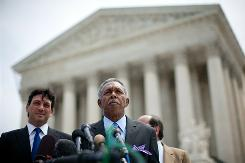 Lead plaintiff Otis McDonald, with his legal team including Alan Gura, left, speaks Monday outside the U.S. Supreme Court building in Washington.