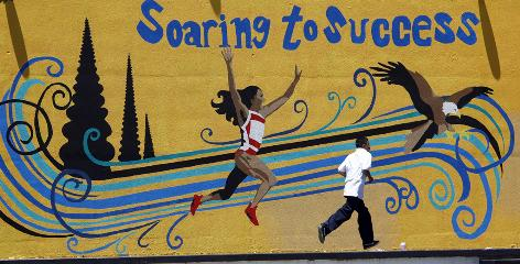 "A student runs by a mural of alumna Florence Griffith-Joyner at Edwin Markham Middle School in South Los Angeles. ""Flo Jo"" was an Olympic medalist sprinter before her death in 1998 at age 38. Markham and a different school, Wonderland Avenue Elementary School, have been featured in debates over California funding cuts."
