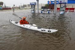 Dennis Barrett paddles his kayak Wednesday down a flooded Padre Boulevard as the early effects of Hurricane Alex are felt along the Texas coast in South Padre Island, Texas.