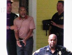 Henry Louis Gates Jr., center, is arrested at his home in Cambridge, Mass., on July 16.
