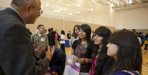 Peter Pitts, an admissions counselor from Monomouth College, talks to Hancock High School 16-year-old juniors, from left, Leticia Gelacio, Yesenia Escobedo and Melissa Gomez during a college fair at Chicago's Westinghouse High School.