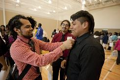 Hector Gonzalez, a post-secondary coach at Hancock High School in Chicago, left, straightens the tie of junior Victor Quito, 18, right, during a college fair, as junior Eddie Ibarra, 17, looks on.