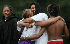 A woman is comforted June 21 at the scene where two bodies were found in Chicago.