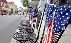 Per tradition, festooned chairs are set out along the Independence Day parade route in Canonsburg, Pa. Ninety percent of the nation's nearly 35 million weekend travelers are expected to take road trips, AAA auto club says.