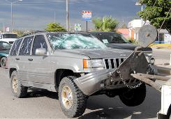 A vehicle involved in the shootout is towed away near the border town of Nogales, Mexico.