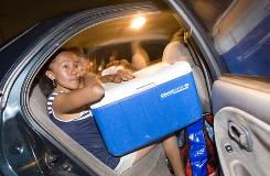 Claudia Suriano, 27, an undocumented immigrant from Mexico, cries in the back seat of her car as she and her family are about to leave Arizona for New Mexico on June 11. After eight years in Arizona the family is moving to New Mexico because of Arizona's new immigration law.