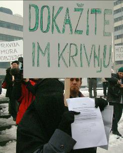 "In this Jan. 25, 2002, file photo Anela Belkacem, wife of deported Algerian Bensayah Belkacem, holds papers she says show by-passers evidence that her husband is innocent, and carries a banner saying ""Prove their guilt"" in front of a Bosnian government building in Sarajevo. In a statement released Friday, July 2, 2010, a three-judge panel in a U.S. federal appeals court reversed a lower court decision that Guantanamo detainee Bensayah's imprisonment was legal; the new decision states he deserves a new lower court review to determine whether he was part of al-Qaeda."