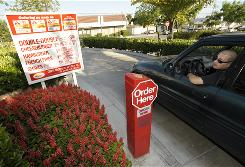 In this June 8, 2010 photo, Paul Rodriguez orders in the drive-through lane at In-N-Out Burger in Baldwin Park, Calif. Amid complaints of obesity and lines of idled cars stretching into neighborhood streets, the town is banning new drive-throughs.