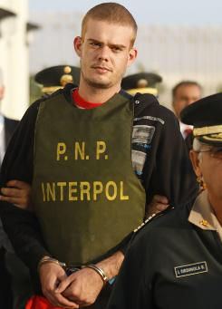 Joran van der Sloot is escorted by police officers outside a Peruvian police station in Tacna, Peru, on June 4.