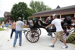 A damaged carriage is taken away in Bellevue, Iowa, on Sunday after the horse that was pulling it got loose and trampled many spectators at a Fourth of July parade.