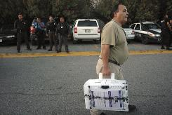 An election worker carries a ballot box full of votes, as state and federal police look on in the northern border city of Ciudad Jurarez, Mexico.