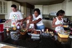 The Hoeltke family, from left, Lance, Milton, Kisa and Maya, prepare a healthy dinner after a day of friendly competition in Prospect, Ky.
