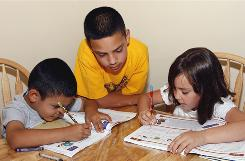 Alex Rodriguez, 11, looks over the shoulders of his younger brother Richard, 4, and sister Alejandra, 7, as they do homework at their home in Denver.