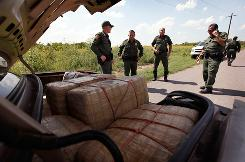 Border Patrol agents examine bales of marijuana in a car near the Mexican border on May 27. In the past two years, Homeland Security officials have seen a rise in kid smugglers around U.S.-Mexico borders.