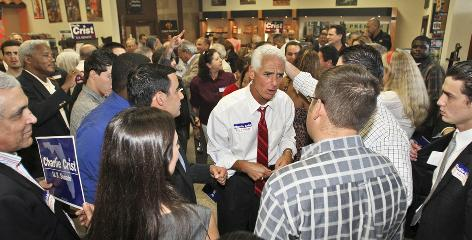 Florida Gov. Charlie Crist, center, talks to supporters at a cigar factory in Miami in May. The Republican-turned-independent now leads the field for the state's U.S. Senate seat.