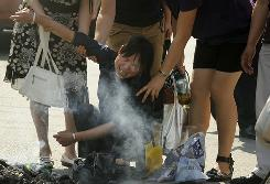 Passersby help a Chinese woman Monday in Urumqi after burning offerings at the site where one of her relatives was killed during the violence that erupted last July between the region's Muslim Uighurs and Han Chinese, the country's dominant ethnic group.