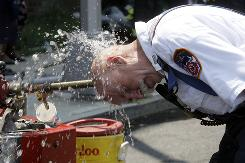 Paul Tauber, a battalion chief with the New York Fire Department, cools himself after firefighters responded to a residential building fire in July in Queens, N.Y.
