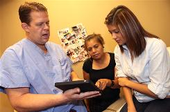 Jeff Livingston uses his iPad to show infomation from his OB/GYN practice's Facebook page to patient Dulce Martinez and her mother, Anastacia, in an exam room in Irving, Texas.