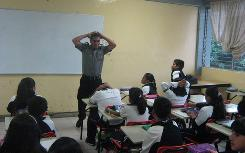 A police officer teaches students how to crawl to safety at the Colegio Mexico in Chilpancingo, Mexico, on Friday.