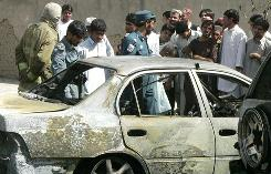 Onlookers, together with Afghan rescue and security personnel, are seen near the wreckage of a burnt-out car at the site of a bomb explosion in Kandahar, Saturday.