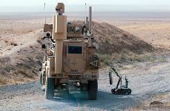 A remote-control robot moves a pressure plate taken from an Improvised Explosive Device (IED) that a unit discovered during a clearance mission Wednesday near Khakriz, Afghanistan.
