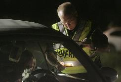 Lee County Sheriff's Office deputy G. Jones, who refused to give his first name, checks a driver's license Friday at a DUI checkpoint.
