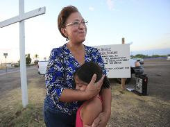 Leticia Ruiz hugs granddaughter Angelina Ramirez after Phoenix service.