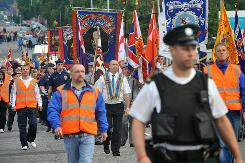 Orangemen march amid tight security past the Nationalist Ardoyne area of North Belfast, Northern Ireland on Monday.