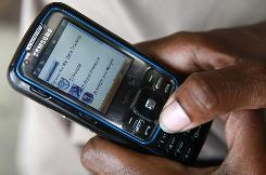 Diabetic Tyrone Harvey, 43, of Washington, looks at the program on his mobile phone that he uses to input his blood glucose levels, blood pressure, height and weight.