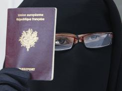 Photo from May 18 shows a woman, who gave her name as Najat, holding her passport during a news conference in Montreuil, east of Paris.