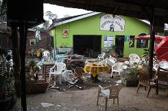 Chairs and tables are strewn outside a restaurant in Kampala, Uganda, after an explosion.
