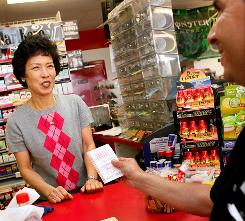 Sun Bae, left, owner of the Times Market, sells lottery tickets to Frank Gutierrez at her store in Bishop, Texas. Bishop native Joan Ginther, who now lives in Las Vegas, won four Texas Lottery jackpots for a combined $21 million, and the last two winning tickets were purchased at Bae's store.