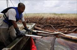 Gerald Ingraham vacuums oil near marsh grass in Barataria Bay on the coast of Louisiana on June 20.
