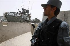 An Afghan policeman stands guard at a police base which came under attack last night in Kandahar, south of Kabul, Afghanistan, Wednesday.