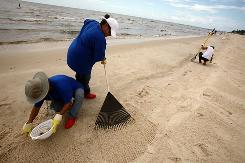 Workers remove tar balls in Waveland, Miss., on Tuesday. Five seafloor leaks were deemed inconsequential