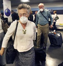 A couple wears masks after flight from Puerto Rico to Boston in November.