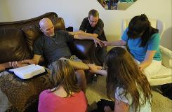"Darren Boyer, center kneeling beside the couch, prays with, from right clockwise, Susan Dennison, Tasha Gustafson and Jolene Larson, asking for God's wisdom regarding an upcoming decision that Brent Tribble, left, will make about his life, during a non-denominational ""house church"" service at Boyer's Brighton, Colo. home. The number of these new, small, organic churches is growing, according to the Barna Group"