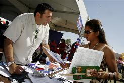 Nevada State Democratic Party outreach director Andres Ramirez gives leaflets and voter registration information to Claudia Ruiz in Las Vegas on April 29, 2007.